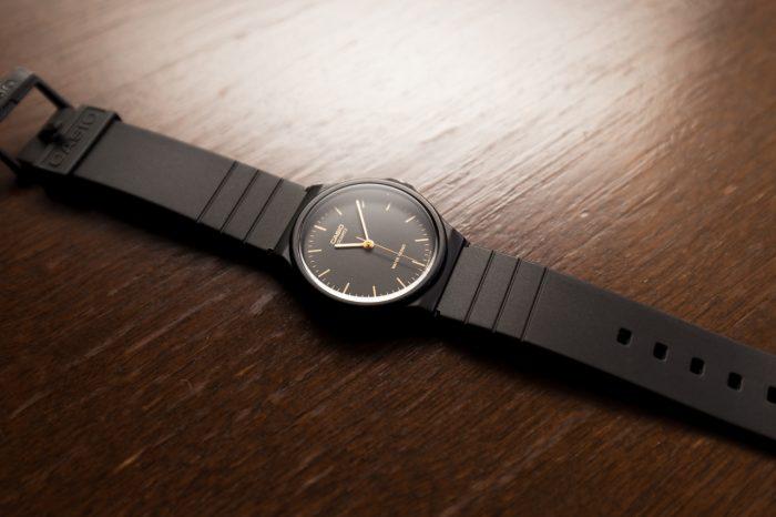 木目のテーブルにカシオの腕時計(チープカシオ)を置いて、奥の壁にバウンス光を当てて逆光のロケーションを作り出した写真
