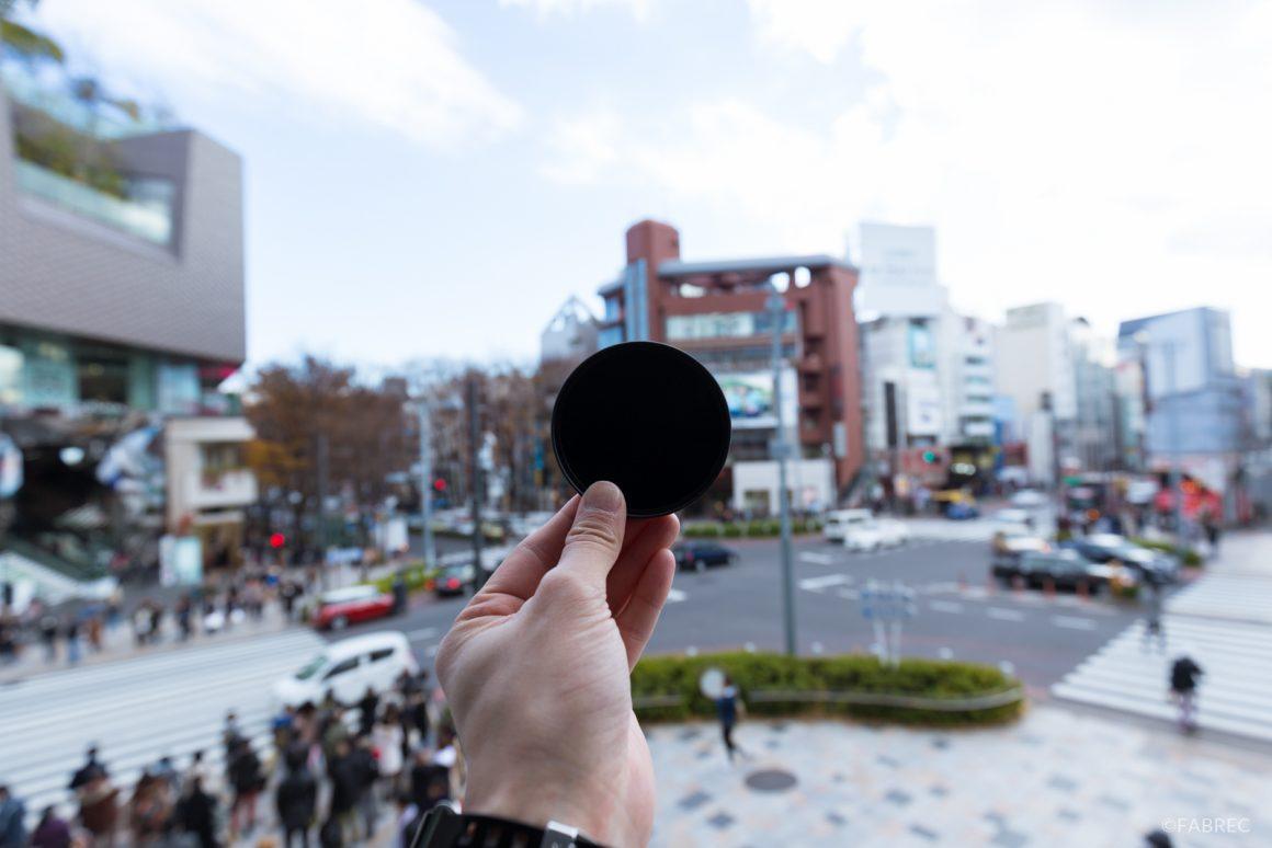 向こう側が見えないほど真っ黒なレンズフィルター。取り付けることで、光を取り込む量を減らし、写真を暗くすることができる。