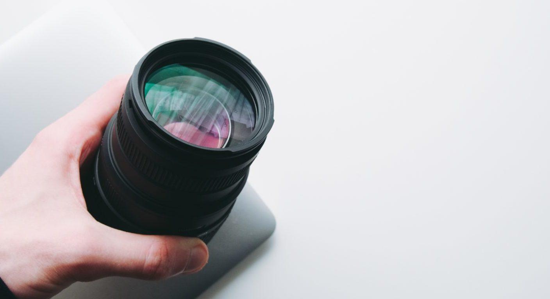 レンズを持つ人の手が写っている様子。イメージ写真